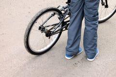 Παιδί που κρατά ένα ποδήλατο στον γκρίζο δρόμο ασφάλτου στοκ εικόνα με δικαίωμα ελεύθερης χρήσης