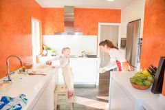 Παιδί που μαγειρεύει και που εξετάζει τη μητέρα στην κουζίνα στοκ φωτογραφίες