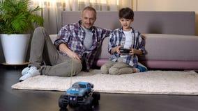 Παιδί που μαθαίνει να οδηγεί το αυτοκίνητο στο ραδιο έλεγχο, ακριβό δώρο από τον πατέρα της Κυριακής στοκ φωτογραφία
