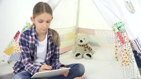 Παιδί που μελετά, παιδί σπουδαστών που χρησιμοποιεί την ταμπλέτα, γράφοντας τη σχολική εργασία, παιχνίδι κοριτσιών απόθεμα βίντεο