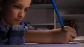 Παιδί που μελετά στη νύχτα, παιδί που γράφει στη μελαχροινή μαθήτρια βραδιού σπουδαστών μαθαίνοντας απόθεμα βίντεο