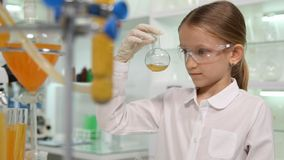 Παιδί που μελετά τη χημεία στο σχολικό εργαστήριο, κορίτσι σπουδαστών που κάνει τα πειράματα στοκ εικόνες
