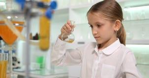 Παιδί που μελετά τη χημεία στο σχολικό εργαστήριο, κορίτσι σπουδαστών που κάνει τα πειράματα 4K φιλμ μικρού μήκους