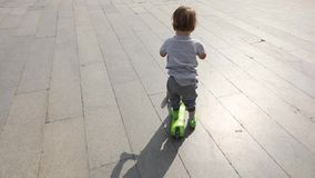 Παιδί που οδηγά το πράσινο μηχανικό δίκυκλο λακτίσματος απόθεμα βίντεο