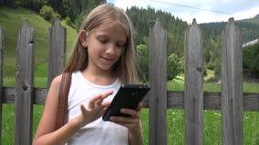 Παιδί που παίζει Smartphone υπαίθριο, παιδί στην ταμπλέτα, χαλάρωση κοριτσιών στη φύση φιλμ μικρού μήκους
