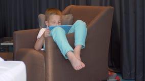 Παιδί που περνά στο σπίτι το ελεύθερο χρόνο με την ψηφιακή ταμπλέτα απόθεμα βίντεο