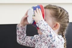 Παιδί που τρώει από το πιάτο που κρατιέται στο πρόσωπό της στοκ εικόνες