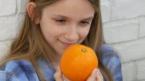 Παιδί που τρώει τα φρούτα πορτοκαλιών στο πρόγευμα, παιδί κοριτσιών που μυρίζει την υγιή κουζίνα τροφίμων απόθεμα βίντεο