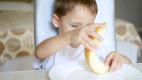 Παιδί που τρώει το πεπόνι, που κάθεται στον πίνακα Η έννοια των υγιών παιδικών τροφών φιλμ μικρού μήκους