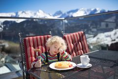 Παιδί που τρώει apres το μεσημεριανό γεύμα σκι Διασκέδαση χειμερινού χιονιού για τα παιδιά Στοκ Φωτογραφίες
