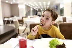 Παιδί που τρώει cutlet κοτόπουλου στοκ φωτογραφία