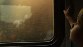 Παιδί που φαίνεται έξω το παράθυρο τραίνων απόθεμα βίντεο