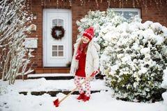 Παιδί που φτυαρίζει το χειμερινό χιόνι Τα παιδιά καθαρίζουν driveway στοκ εικόνες