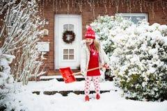 Παιδί που φτυαρίζει το χειμερινό χιόνι Τα παιδιά καθαρίζουν driveway στοκ εικόνα