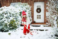Παιδί που φτυαρίζει το χιόνι Μικρό κορίτσι με driveway καθαρίσματος φτυαριών μετά από τη χειμερινή χιονοθύελλα Τα παιδιά καθαρίζο στοκ φωτογραφίες
