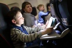 Παιδί που χρησιμοποιεί την ταμπλέτα στο αεροπλάνο στοκ εικόνες