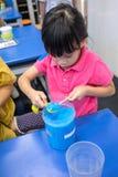 Παιδί που χρησιμοποιεί chopstick για να ισοπεδώσει την μπλε χημική ουσία στη μέτρηση της SP Στοκ φωτογραφία με δικαίωμα ελεύθερης χρήσης