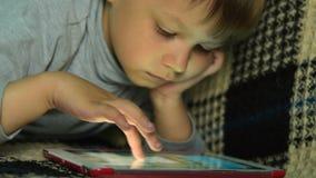Παιδί που ψάχνει για το παιχνίδι στην ψηφιακή ταμπλέτα φιλμ μικρού μήκους