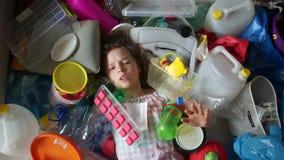 Παιδί σε έναν σωρό των πλαστικών αποβλήτων Πλαστική έννοια στάσεων Το κορίτσι άντεξε το χέρι της και ζητά τη βοήθεια Βοηθήστε τον απόθεμα βίντεο