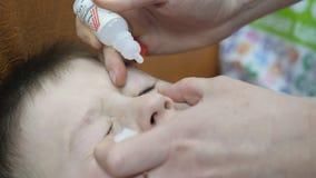 Παιδί σε μια οφθαλμική κλινική Ενστάλαξη των πτώσεων ματιών σε ένα μικρό αγόρι φιλμ μικρού μήκους