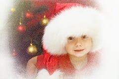 Παιδί σε Santa ΚΑΠ με το χριστουγεννιάτικο δέντρο στο παράθυρο Παιδί και χιονοπτώσεις στοκ φωτογραφία με δικαίωμα ελεύθερης χρήσης