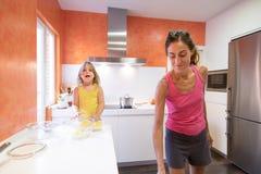 Παιδί στην κουζίνα που κοιτάζει και που μιλά δίπλα στη μητέρα στοκ φωτογραφία με δικαίωμα ελεύθερης χρήσης