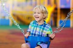 Παιδί στην παιδική χαρά τα παιδιά ταλάντευσης παίζουν υπαίθριο στοκ φωτογραφία