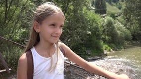Παιδί στη γέφυρα στα βουνά, παιδί που στη φύση, κορίτσι που φαίνεται ένας ποταμός, ρεύμα απόθεμα βίντεο