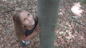 Παιδί στο δάσος, παιχνίδι παιδιών στη φύση, κορίτσι στην περιπέτεια υπαίθρια πίσω από ένα δέντρο στοκ εικόνα με δικαίωμα ελεύθερης χρήσης