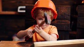 Παιδί στο χαριτωμένο παιχνίδι κρανών ως οικοδόμο ή επιδιορθωτή, την επισκευή ή Καρφί σφυρηλάτησης αγοριών παιδιών στον ξύλινο πίν φιλμ μικρού μήκους