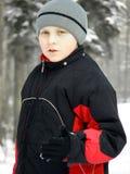 Παιδί στο χιόνι στα θερμά ενδύματα στοκ εικόνες