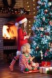 Παιδί στο χριστουγεννιάτικο δέντρο Παιδιά στην εστία στα Χριστούγεννα στοκ εικόνες με δικαίωμα ελεύθερης χρήσης