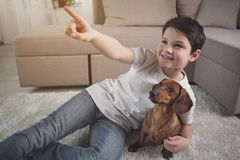 Παιδί Dreamful που έχει τη διασκέδαση με το κουτάβι του Στοκ Φωτογραφία
