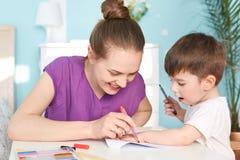 Παιδιά, έννοια τέχνης και εκπαίδευσης Η χαμογελώντας καλή νέα μητέρα επισύρει την προσοχή την τυπωμένη ύλη φοινικών του γιου της  Στοκ Εικόνα