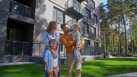 Παιδιά αγκαλιασμάτων μητέρων και πατέρων πλησίον με το νέο σπίτι φιλμ μικρού μήκους