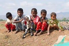 Παιδιά αιγών herder που κάθονται και που κρατούν μια αίγα μωρών, Pune Στοκ Εικόνες