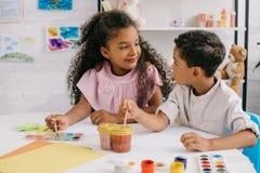 παιδιά αφροαμερικάνων εξετάζοντας ο ένας τον άλλον whdrawing εικόνες με τα χρώματα και τις βούρτσες χρωμάτων στοκ εικόνες με δικαίωμα ελεύθερης χρήσης