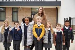 Παιδιά δημοτικού σχολείου που στέκονται μπροστά από το σχολείο με το δάσκαλό τους που κοιτάζει στη κάμερα, μπροστινή άποψη στοκ εικόνα