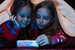 Παιδιά και έννοια τεχνολογίας Κορίτσια με τα περίεργα πρόσωπα που εξετάζουν την τηλεφωνική οθόνη στοκ φωτογραφία