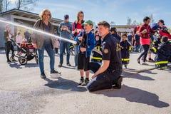 Παιδιά και γονείς σε έναν πυροσβεστικό σταθμό που δοκιμάζει μια μάνικα πυρκαγιάς στοκ φωτογραφία