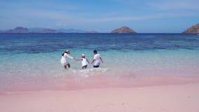 Παιδιά και μητέρα που τρέχουν στη ρόδινη παραλία φιλμ μικρού μήκους