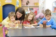 Παιδιά και παιχνίδι εκπαιδευτικών στον παιδικό σταθμό στοκ φωτογραφία
