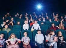 Παιδιά και teens κινούμενα σχέδια προσοχής στον κινηματογράφο και έκφραση των διαφορετικών συγκινήσεων Στοκ Φωτογραφία