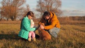Παιδιά με τον πατέρα που κτυπιέται και που παίζεται με το σκυλί στον τομέα φθινοπώρου φιλμ μικρού μήκους
