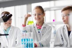 Παιδιά με τους σωλήνες δοκιμής που μελετούν τη χημεία στο σχολείο στοκ εικόνες