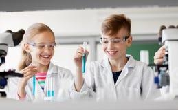 Παιδιά με τους σωλήνες δοκιμής που μελετούν τη χημεία στο σχολείο στοκ εικόνα με δικαίωμα ελεύθερης χρήσης