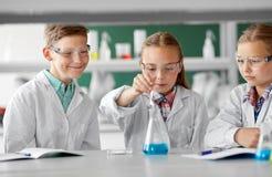 Παιδιά με το σωλήνα δοκιμής που μελετούν τη χημεία στο σχολείο στοκ φωτογραφία
