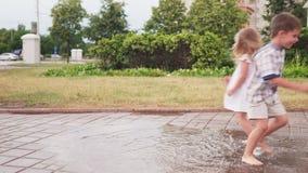 Παιδιά που έχουν τη διασκέδαση και χωρίς παπούτσια που παίζουν στη λακκούβα μετά από τη βροχή στο πάρκο απόθεμα βίντεο