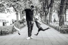 Παιδιά που έχουν τη διασκέδαση με τον μπαμπά στο πάρκο Στοκ Εικόνες