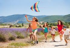 Παιδιά που έχουν τη διασκέδαση που πετά το ζωηρόχρωμο ικτίνο το καλοκαίρι στοκ φωτογραφία